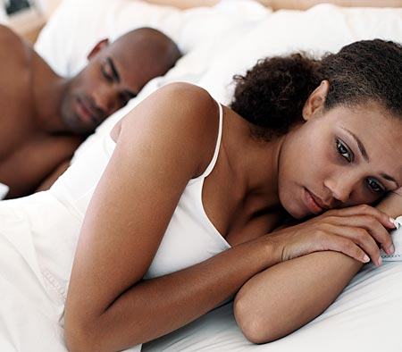 Wife turning away from her husband in bed, seemingly worried. | Source: Flickr