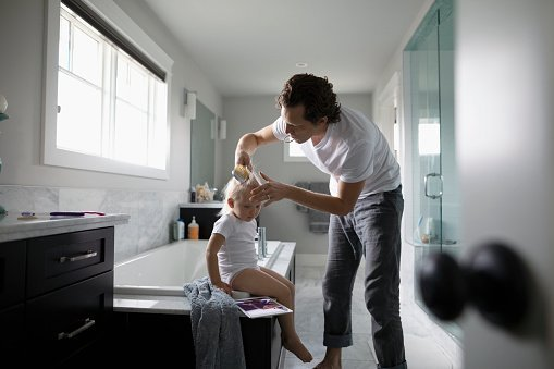 A father brushing his daughter's hair.| Photo: Getty Images.