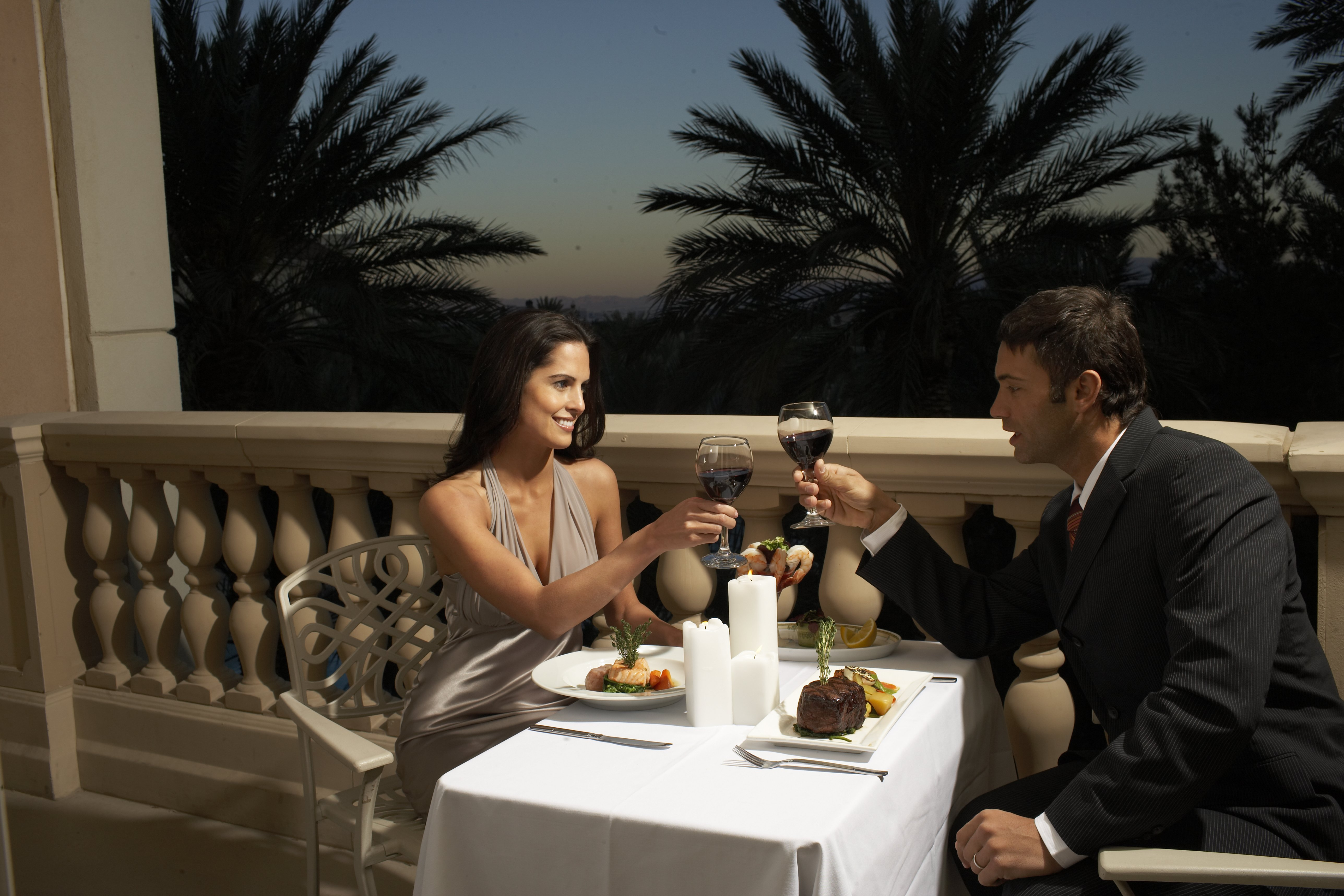 Photo of couple in evening wear having dinner on balcony, toasting with red wine | Photo: Getty Images