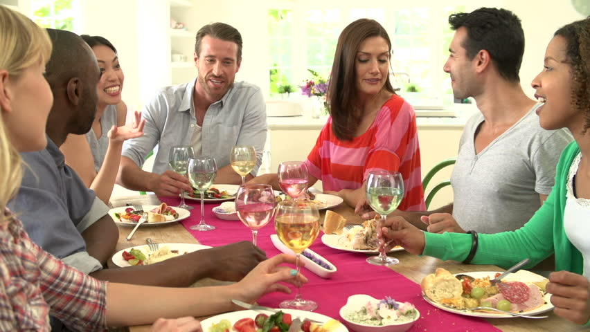 Young adults having a dinner party | Photo: Shutterstock