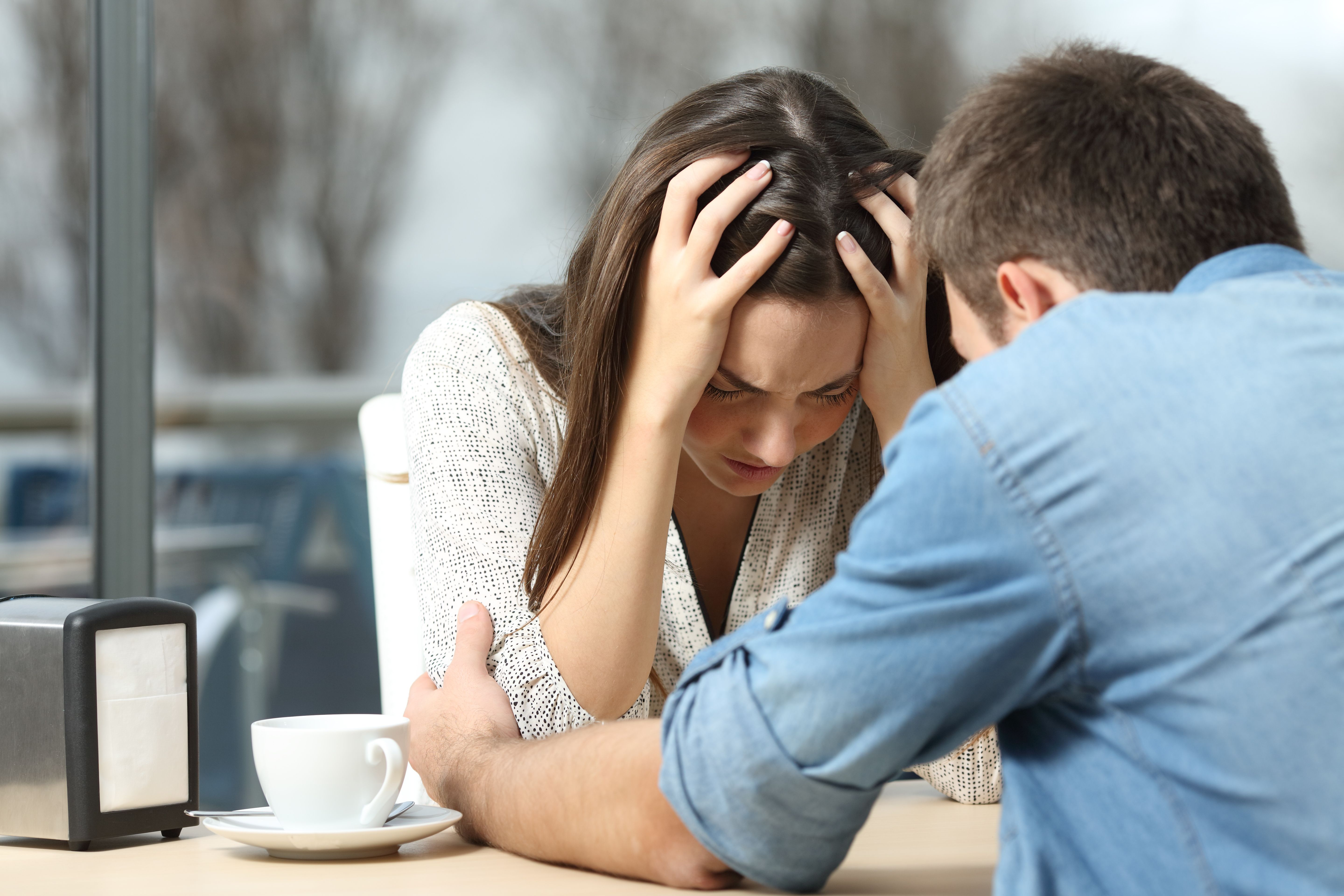 Woman looking stressed with her hands on her head while engaging with a man.   Photo: Shutterstock