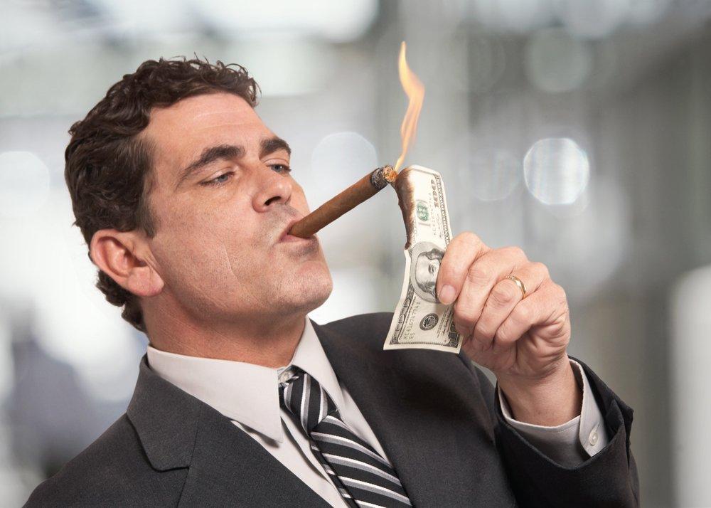 Un riche homme d'affaires qui allume des cigarettes avec un billet de 100 $. | Source : Shutterstock