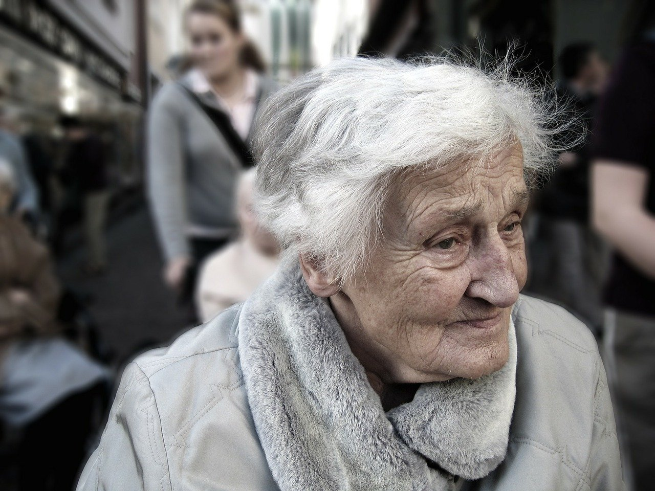 A close-up of an older woman with others behind her   Photo: Pixabay/Gerd Altmann