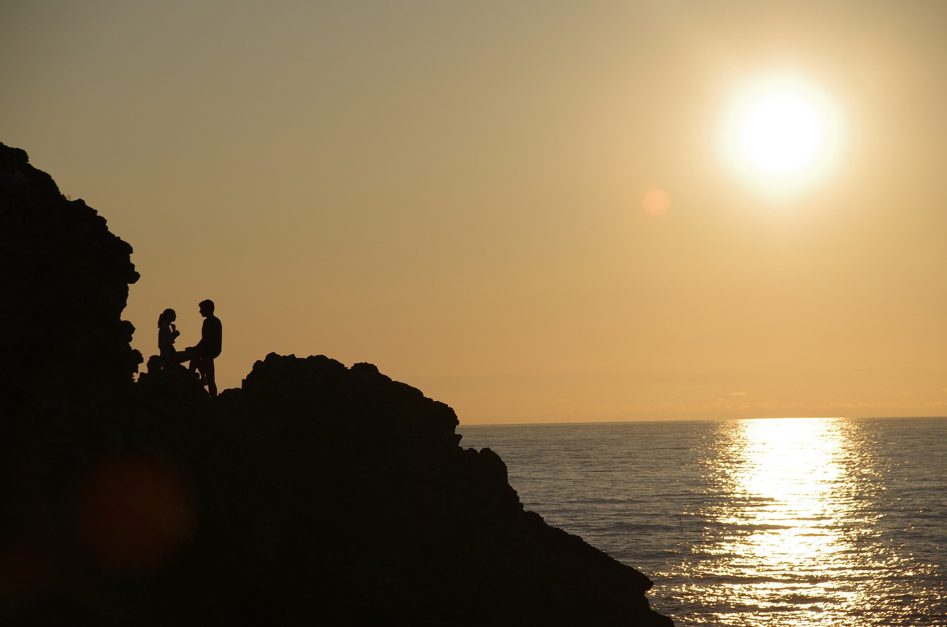 A couple on a cliff at sunset.   Pixabay/alberto uganelli