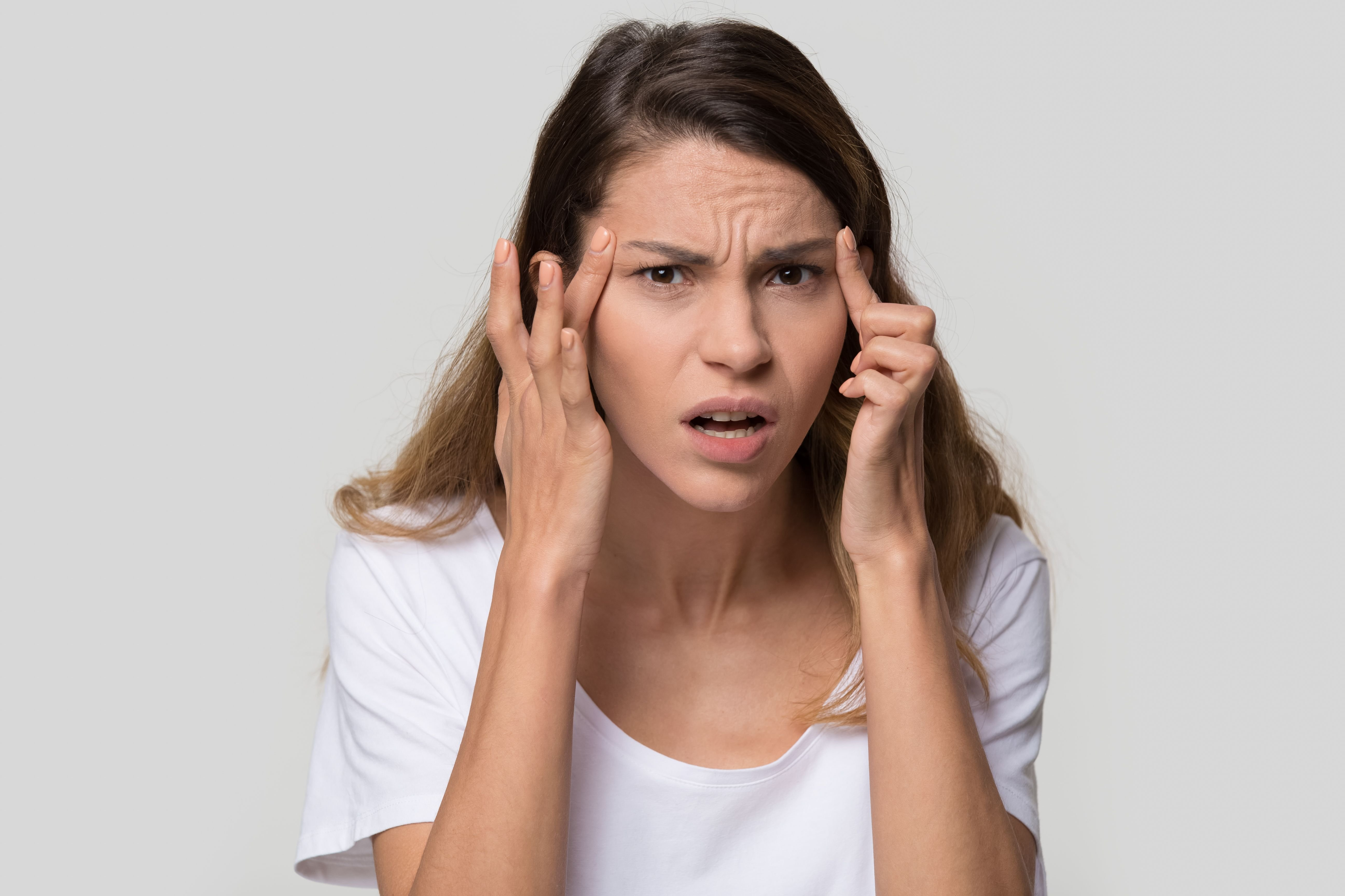 A woman fed up while holding her face. | Source: Shutterstock