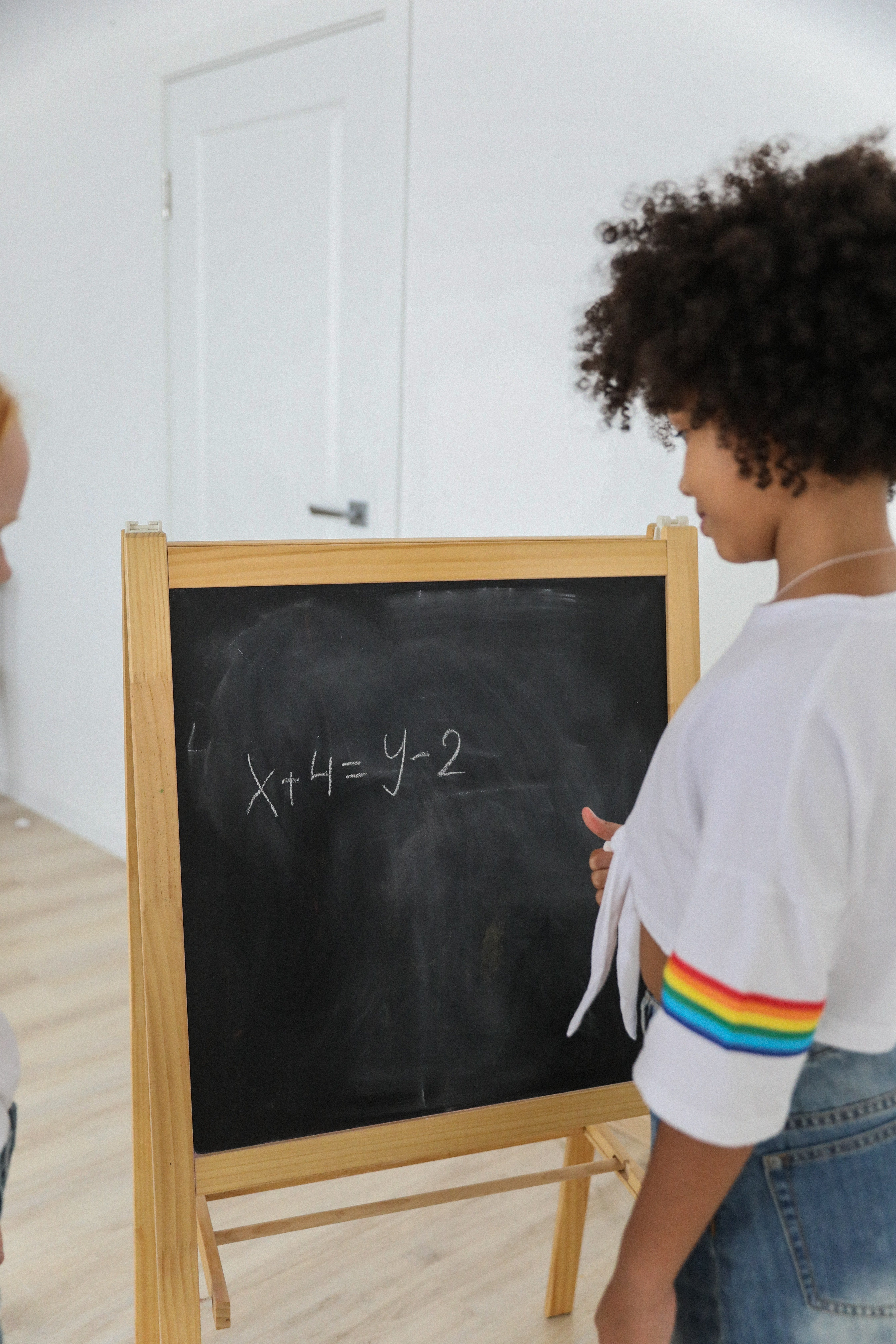 A girl attempts to figure out the equation on the chalkboard in front of her | Photo: Pexels
