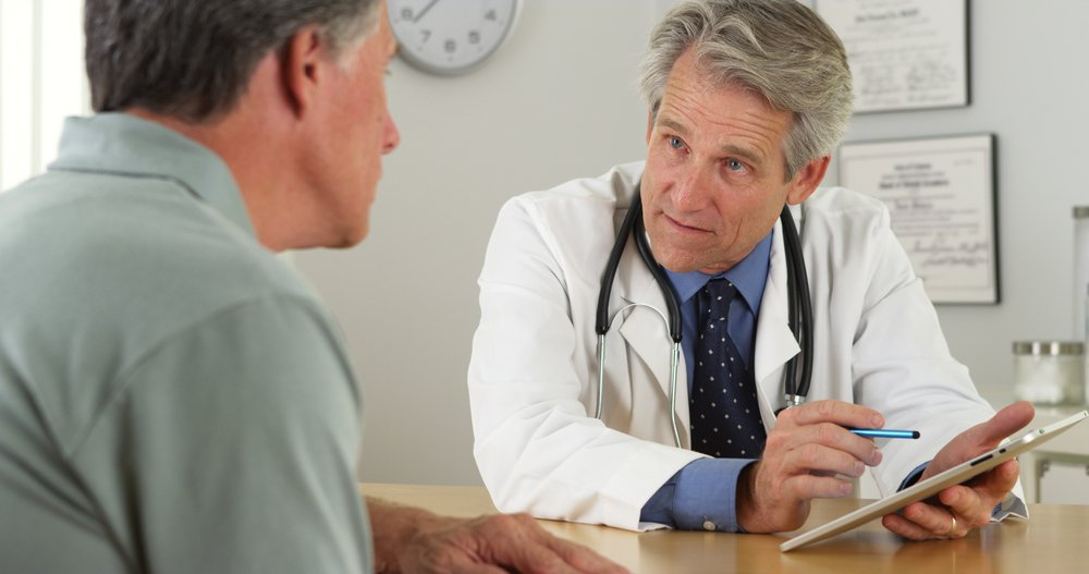 A doctor talking with a patient in the office. | Photo: Shutterstock