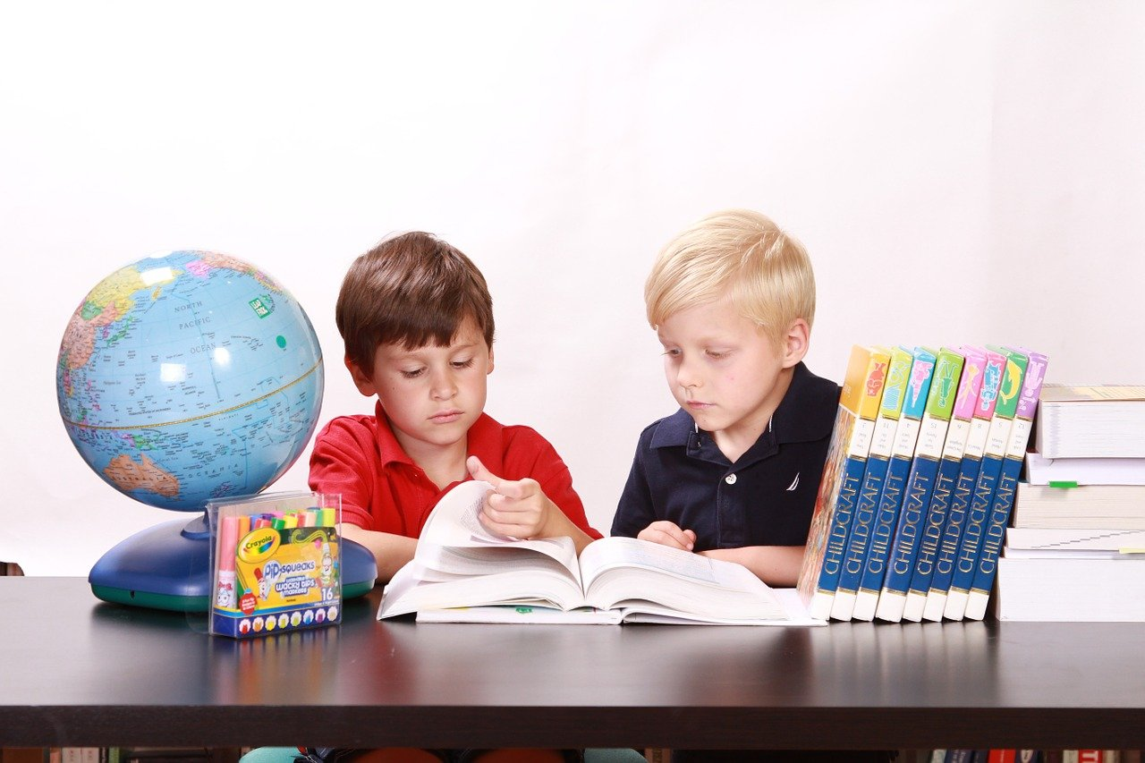 A photo of two young boys reading a book. | Photo: Pixabay
