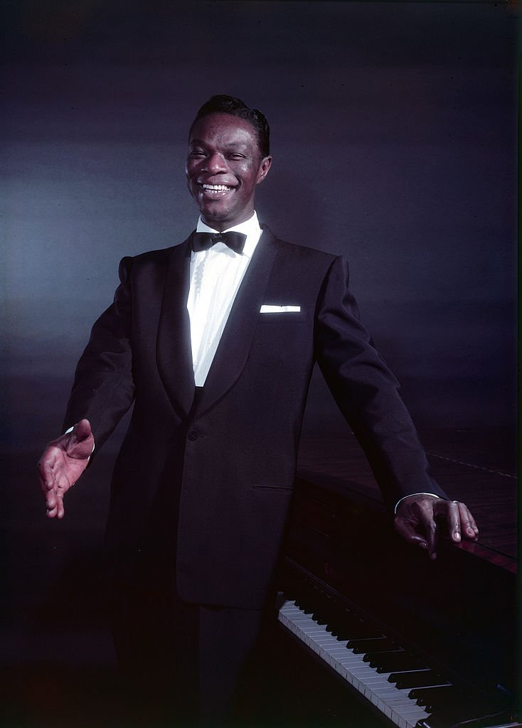Nat King Cole dressed in formal wear, as he poses in front of a piano, 1954. | Photo: Getty Images.