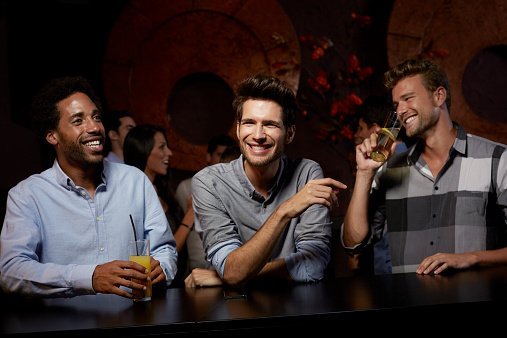 Photo of a cheerful male friends enjoying while having drinks in nightclub | Photo: Getty Images