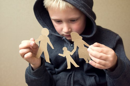 Child with broken paper family cut-out. | Source: Shutterstock.