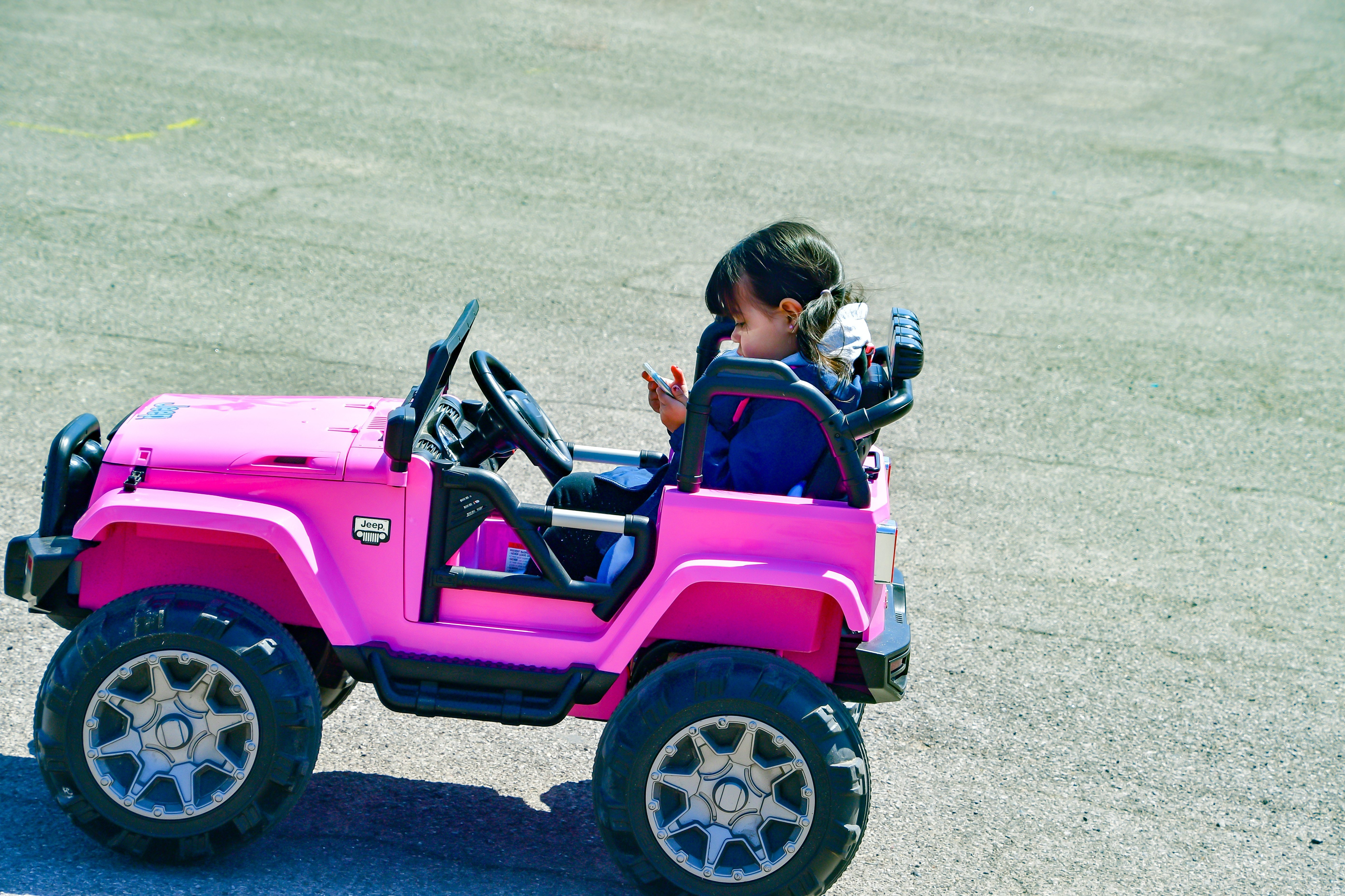 A little girl texting in her toy car. | Source: Shutterstock