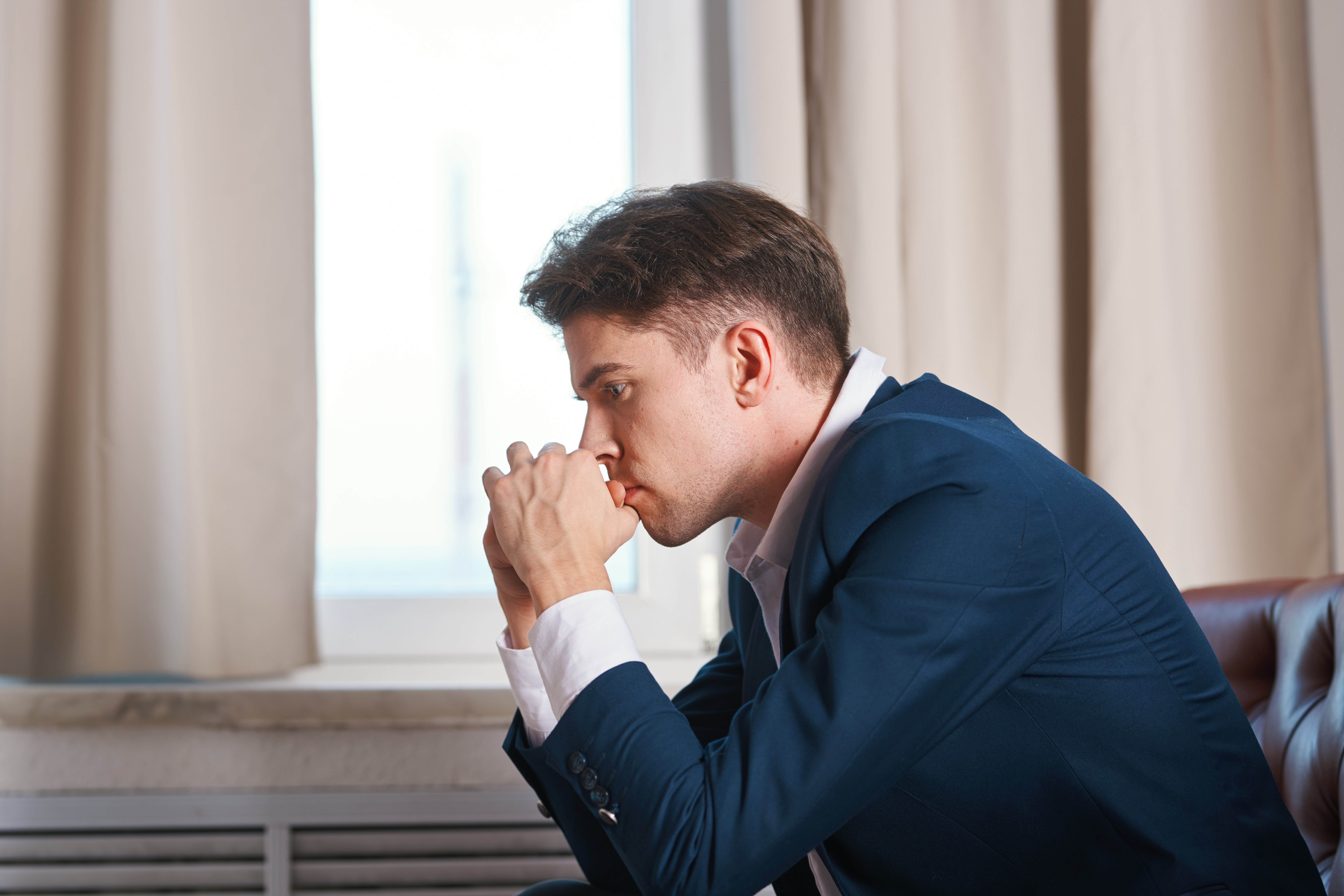 A business man holds his hands near the face with a pensive look of depression melancholy   Photo: Shutterstock.com
