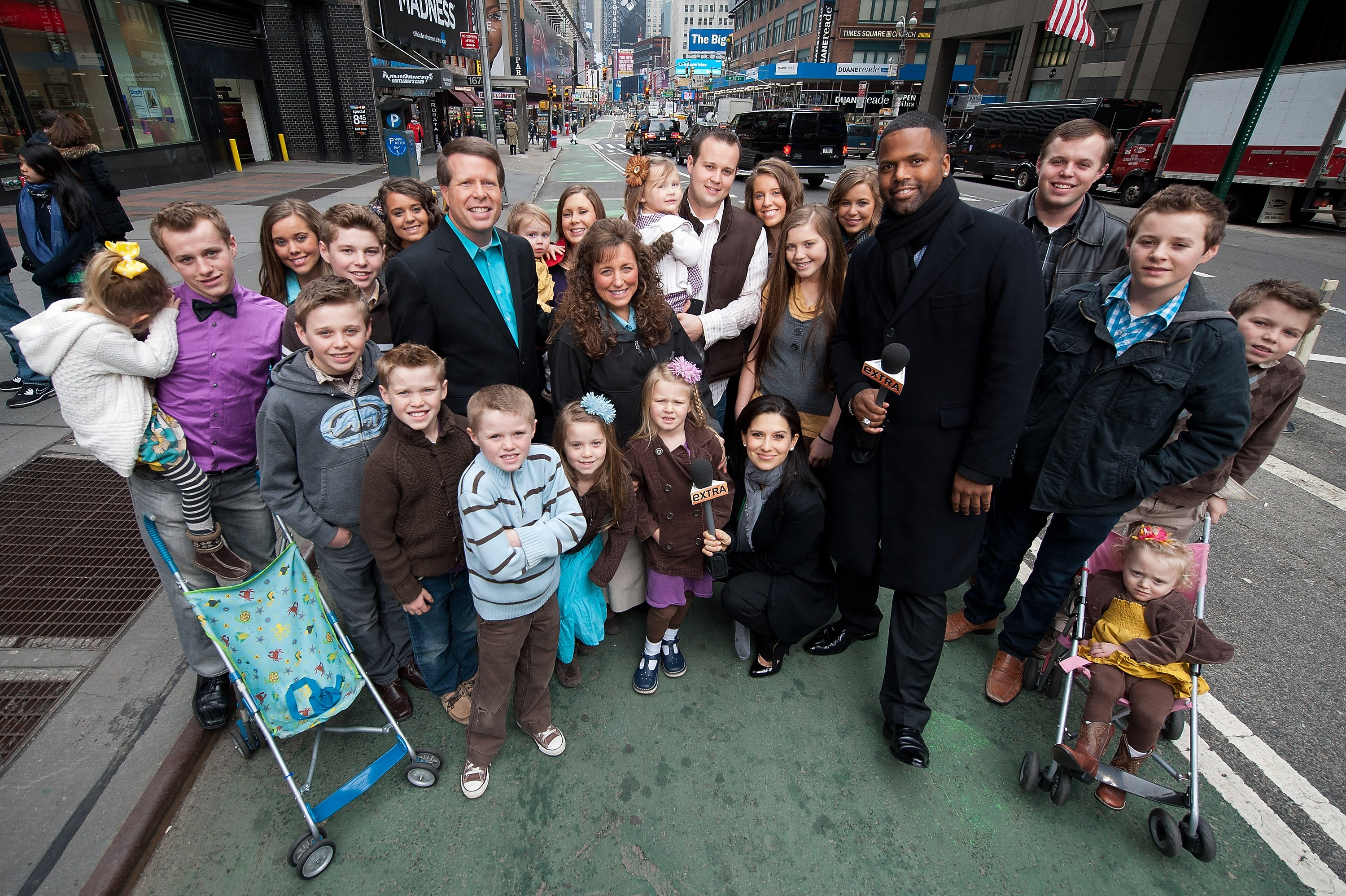 "Jim Bob and Michelle Duggar with their sons and grandchildren during their 2013 visit to ""Extra"" show in New York City. 