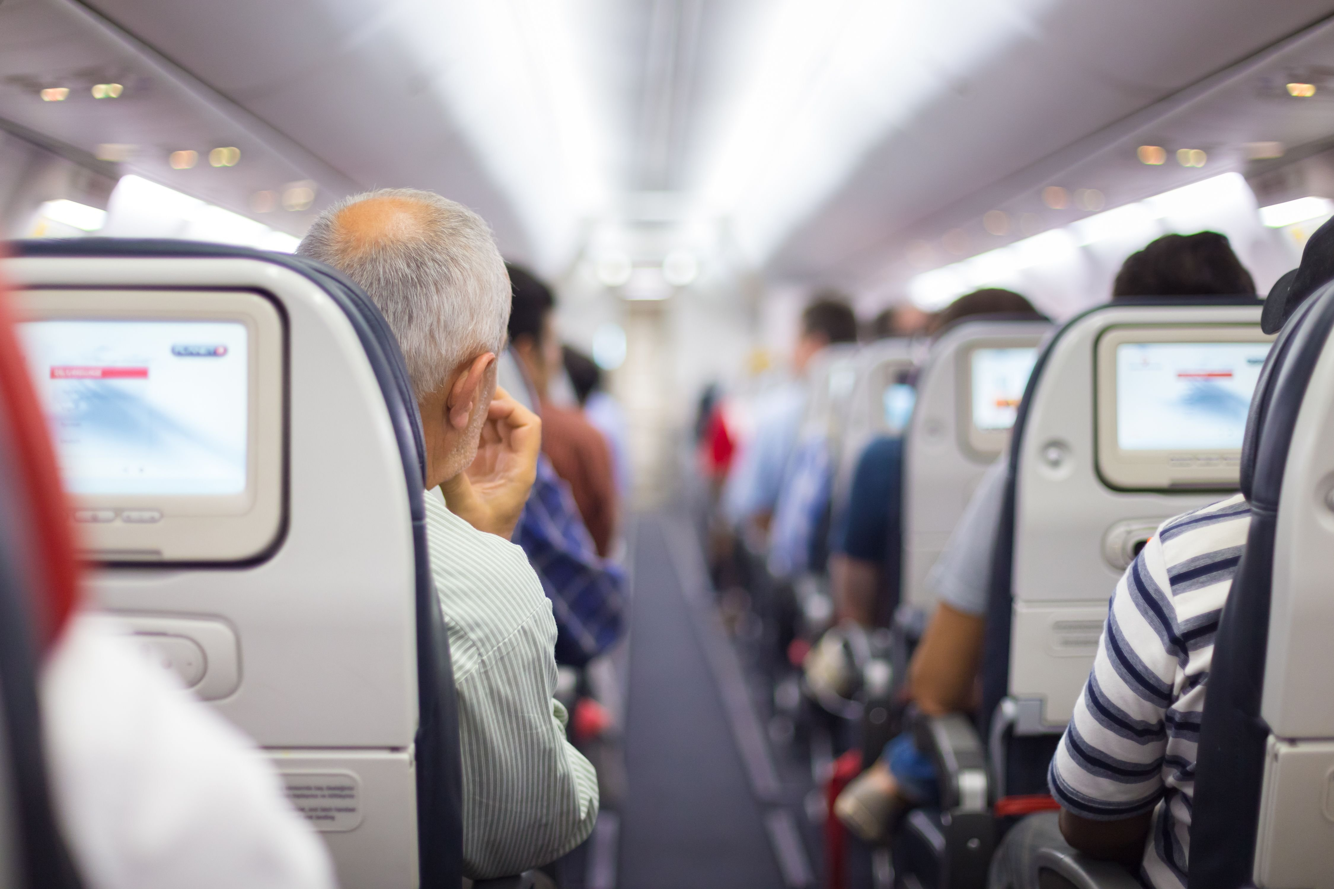 An airplane aisle taken from behind. | Source: Shutterstock