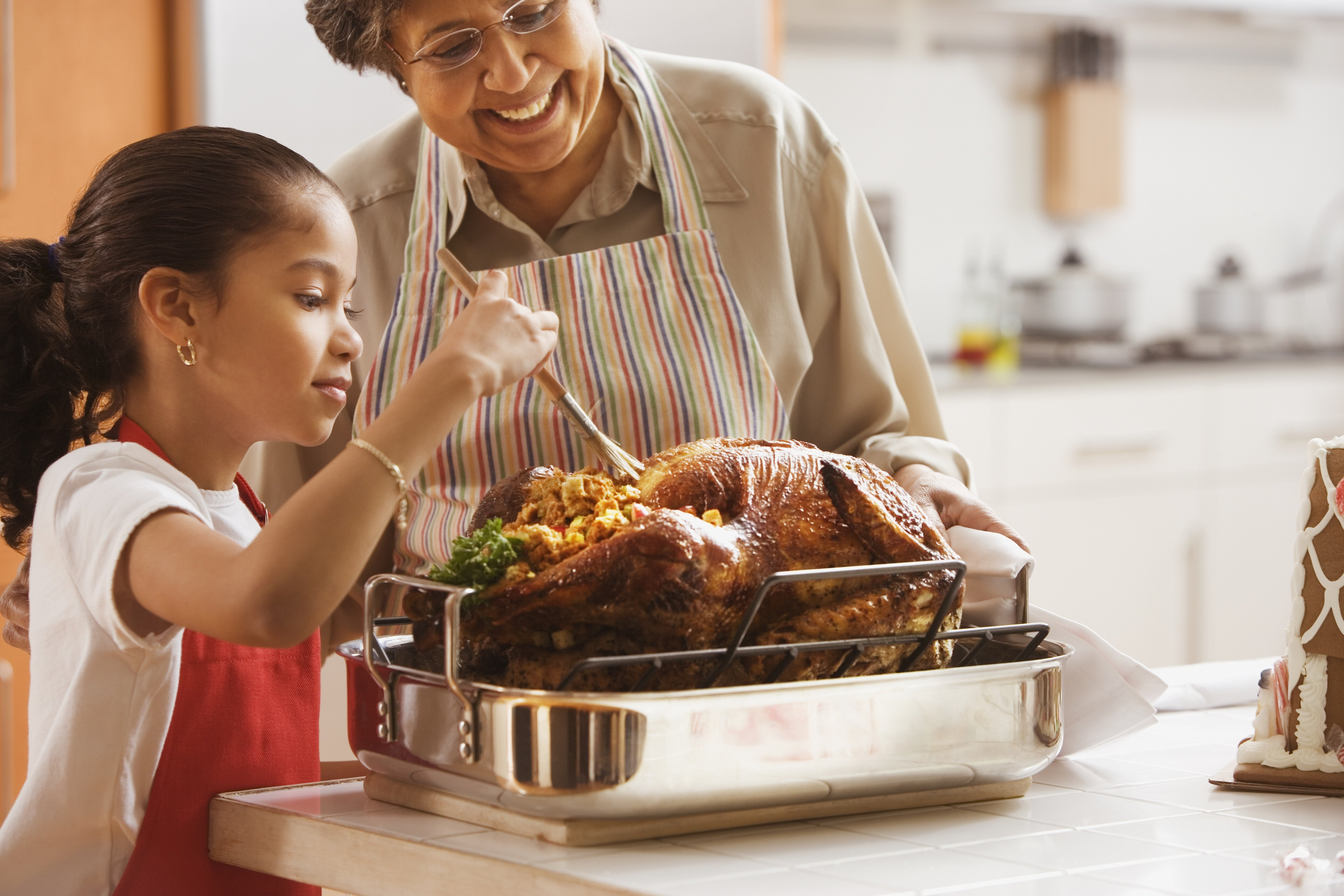 Hispanic granddaughter helping grandmother baste turkey|Photo: Getty Images