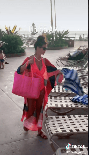 A woman placing water bottles and towels on top of lounge chairs to reserve them.   Source: tiktok.com/sarah_jade