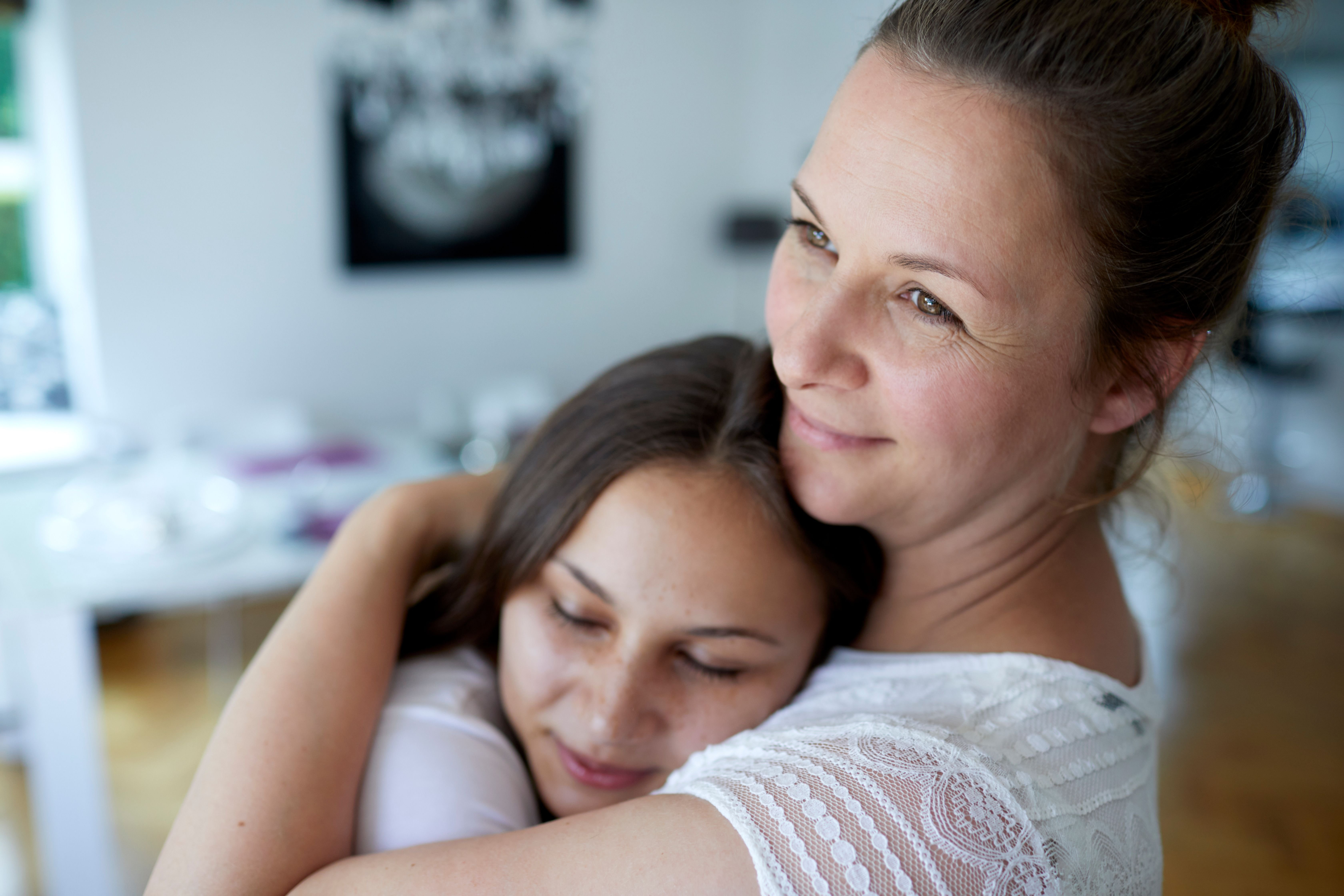 A mother and her teen daughter hugging at home.   Source: Getty Images