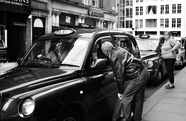 Two men in a car and an elderly man.| Photo: Getty Images.