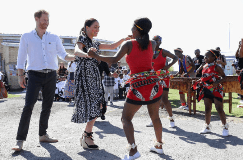 During their royal tour of Africa, Meghan Markle and Prince Harry dance with locals during a visit at the Justice Desk initiative in Nyanga township, on September 23, 2019, Cape Town, South Africa | Source: Getty Images