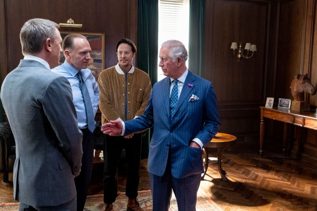 "Prince charles speaks to actors Ralph Fiennes, Daniel Craig, and Director Cary Joji Fukunaga during a tour of the new ""James Bond"" film set in June 2019 