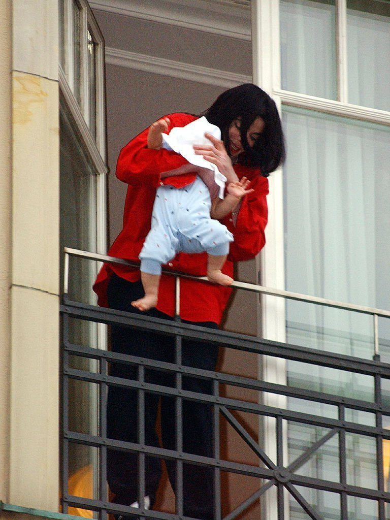 Michael Jackson holds his eight-month-old son Prince Michael II over the balcony of the Adlon Hotel November 19, 2002. | Photo: GettyImages