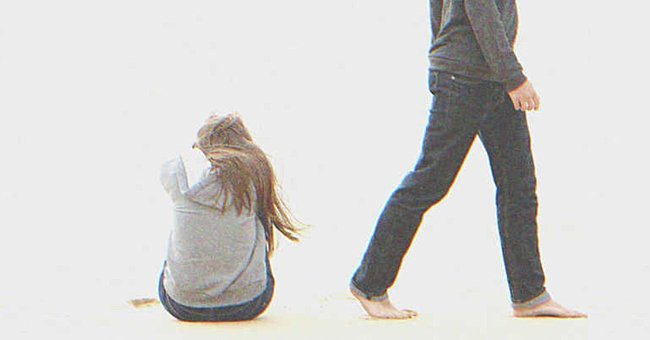 A woman sitting on the ground while a man walks away.   Source: Shutterstock
