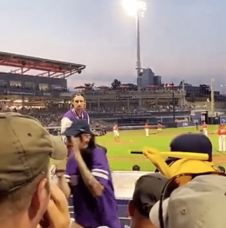 A woman lifts up her hands in disbelief because her partner has just proposed in front of a packed stadium | Photo: Instagram/wtwmass