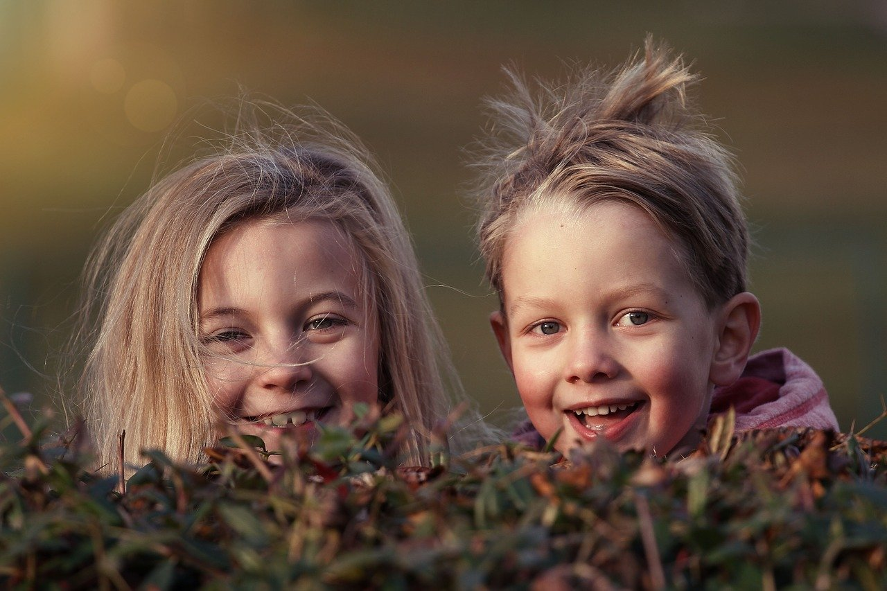 Two children smiling while looking ruffled up while playing in the bushes | Photo: Pixabay/Lenka Fortelna