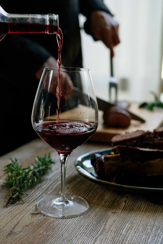 Pouring a glass of red wine   Source: Unsplash