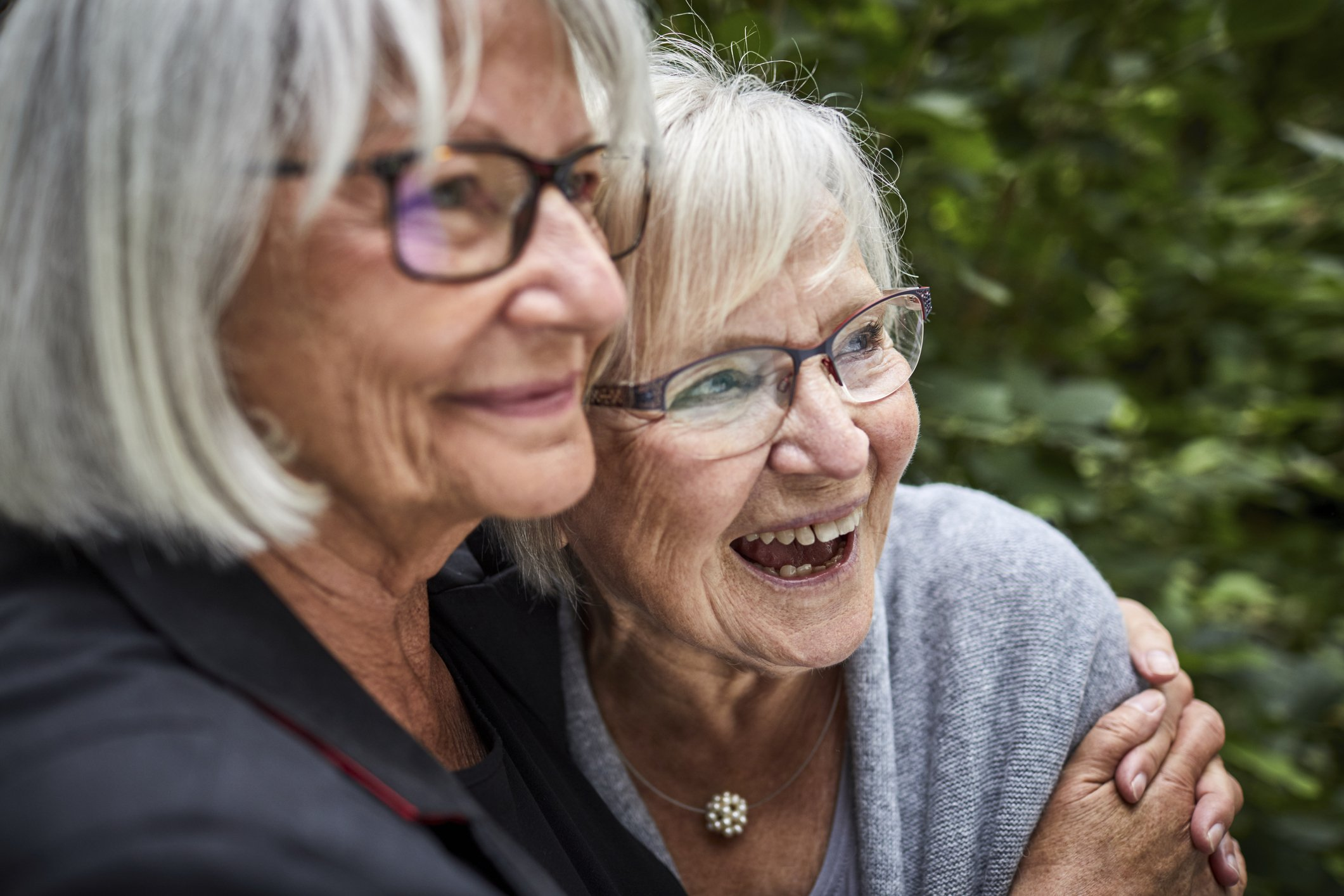 An image showing two senior women hugging each other in a garden. | Photo: Getty Images