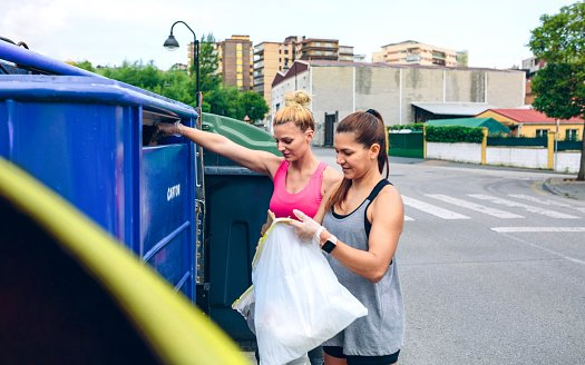 Photo of two girls throwing garbage to recycling dumpster | Photo: Getty Images