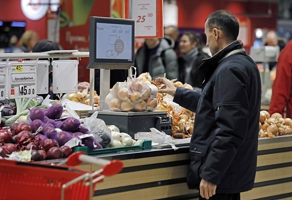 A man pictured shopping for onions in a grocery store | Photo: Getty Images