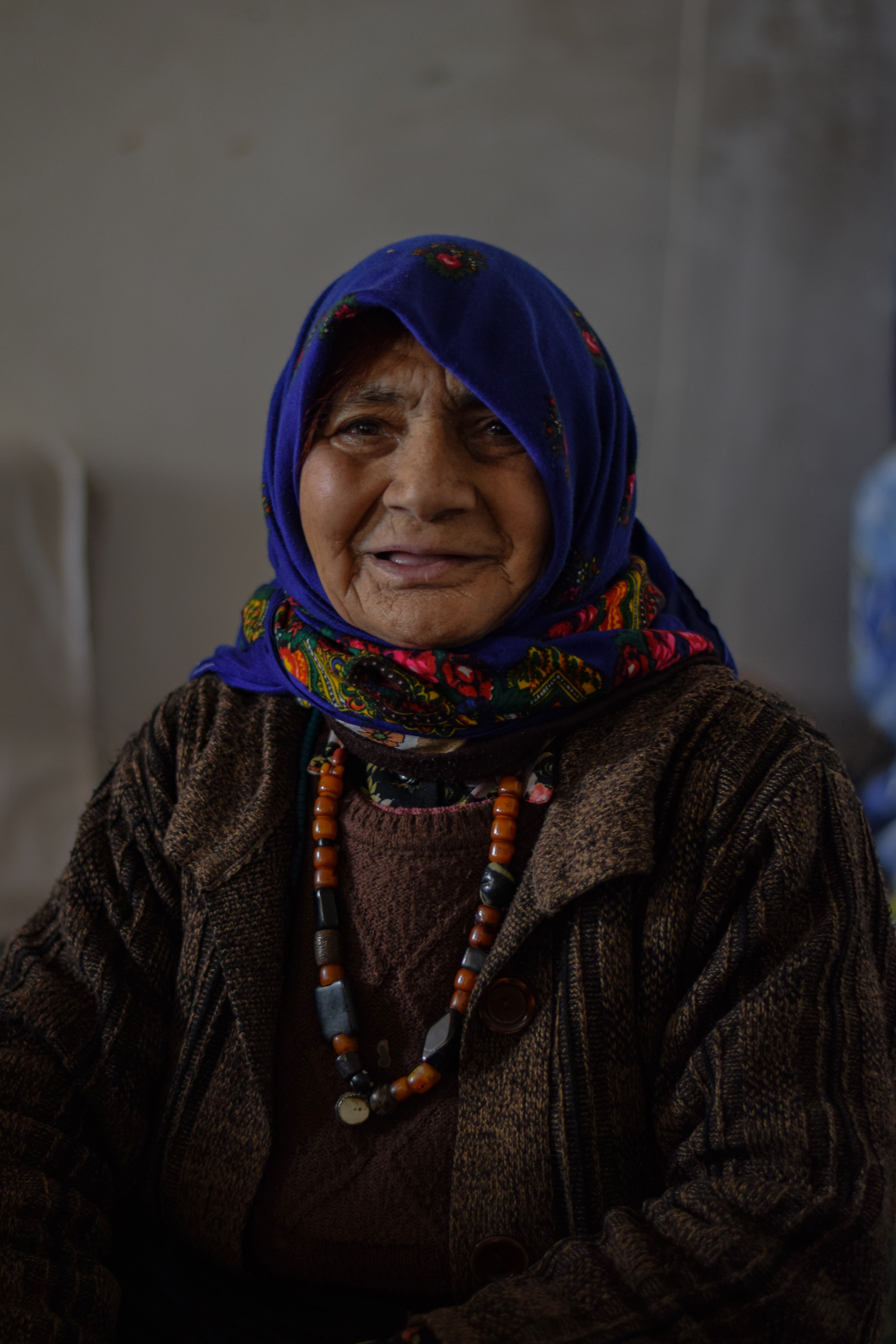 An old woman wearing a blue scarf. | Source: Unsplash