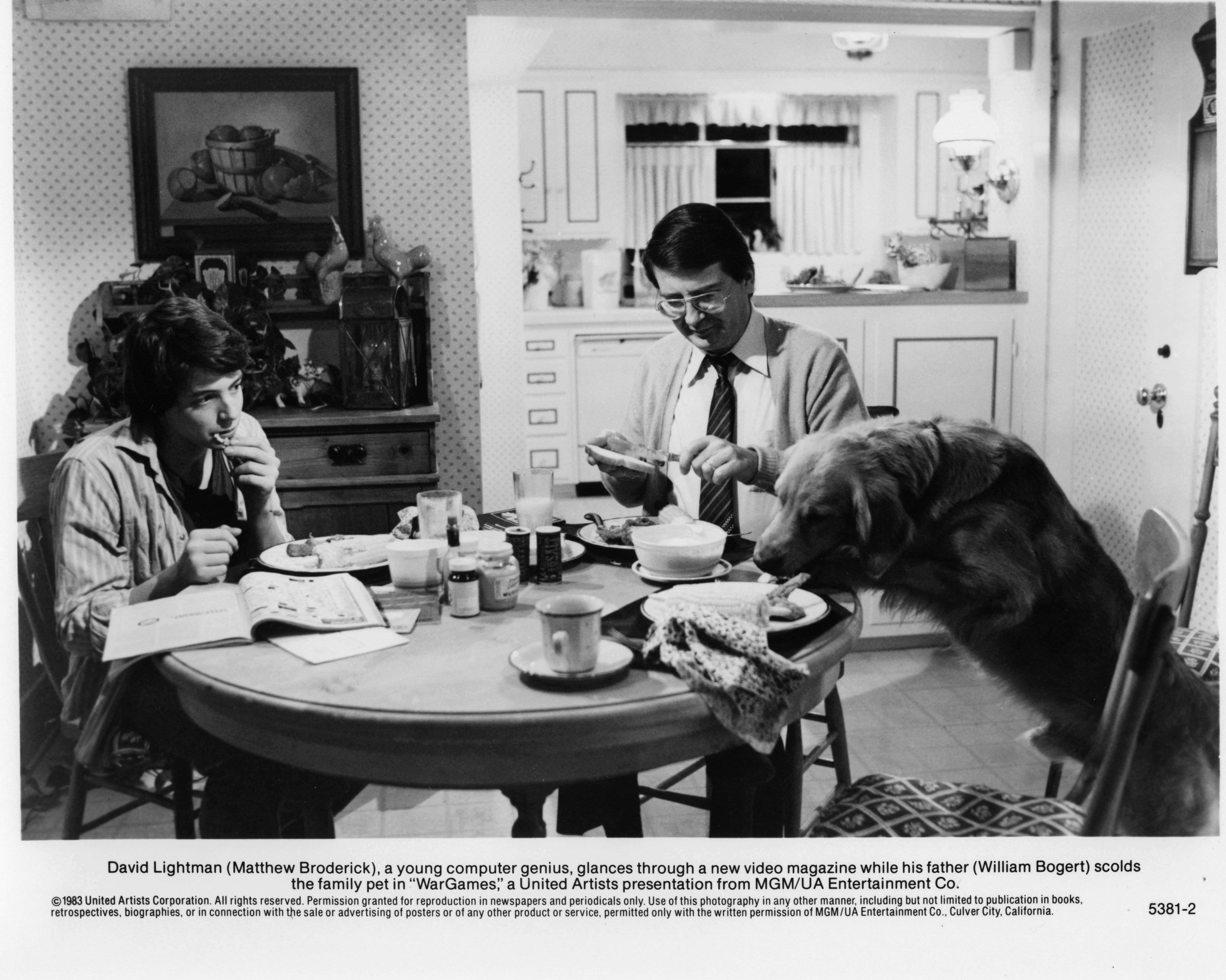 "Matthew Broderick reads a video game magazine at the table with William Bogert in a scene for the ""WarGames"" circa 1983 