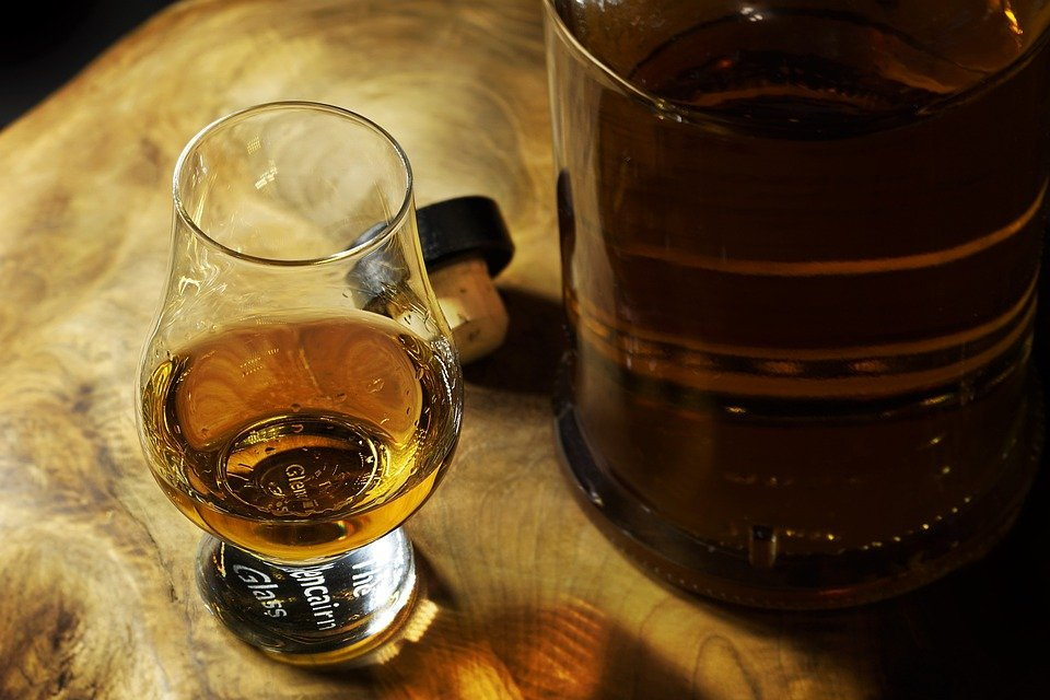 A shot of whiskey in a glass seating next to the whiskey bottle   Photo: Pixabay