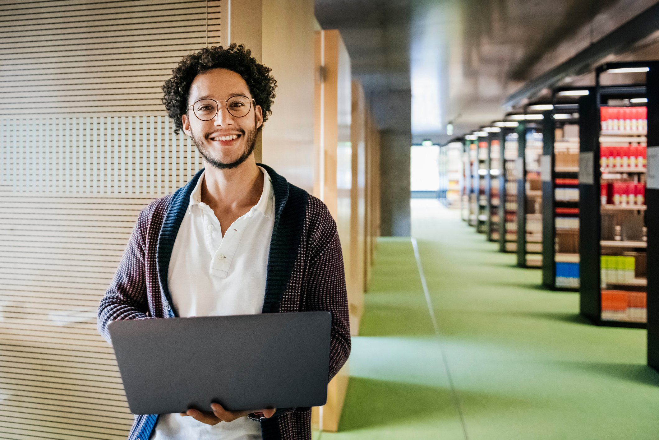A portrait of a young man smiling and holding a laptop in a modern public library.   Photo: Getty Images