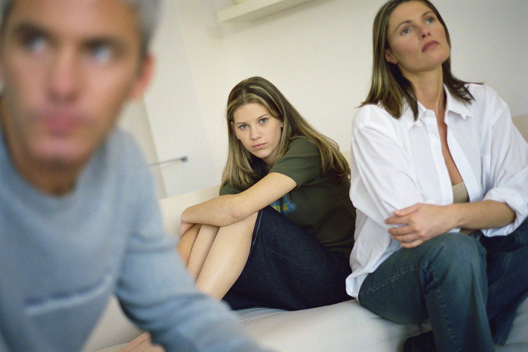 Teenage girl sitting on a bed hugging her knees as her parents sit nearby and look away | Photo: Getty Images
