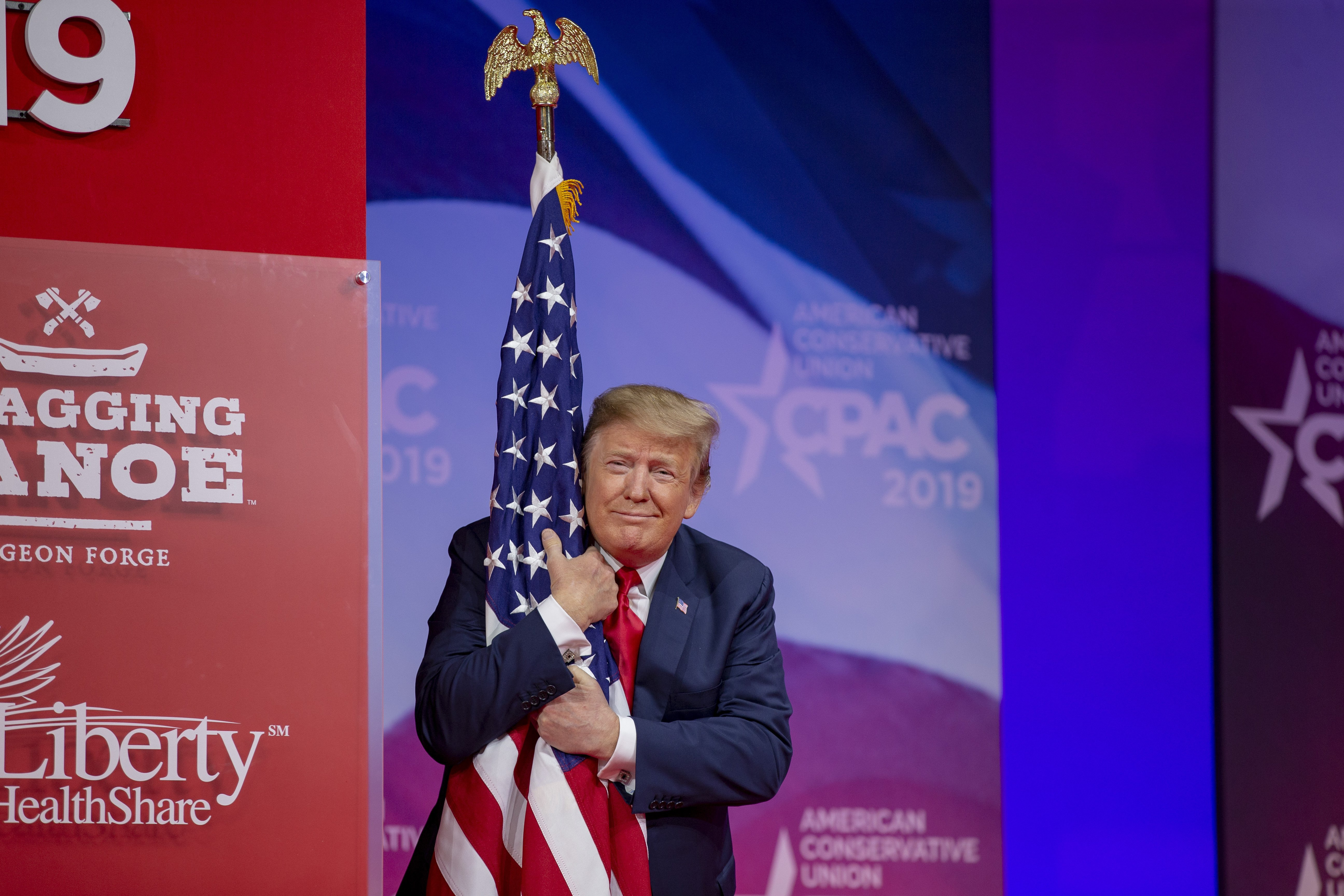 Donald Trump hugging the American flag at the 2019 CPAC in Maryland | Photo: Getty Images