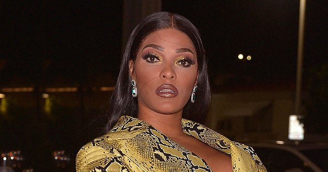 Joseline Hernandez Stuns Posing in White Feathered Dress with High Heels & Matching Chanel Bag