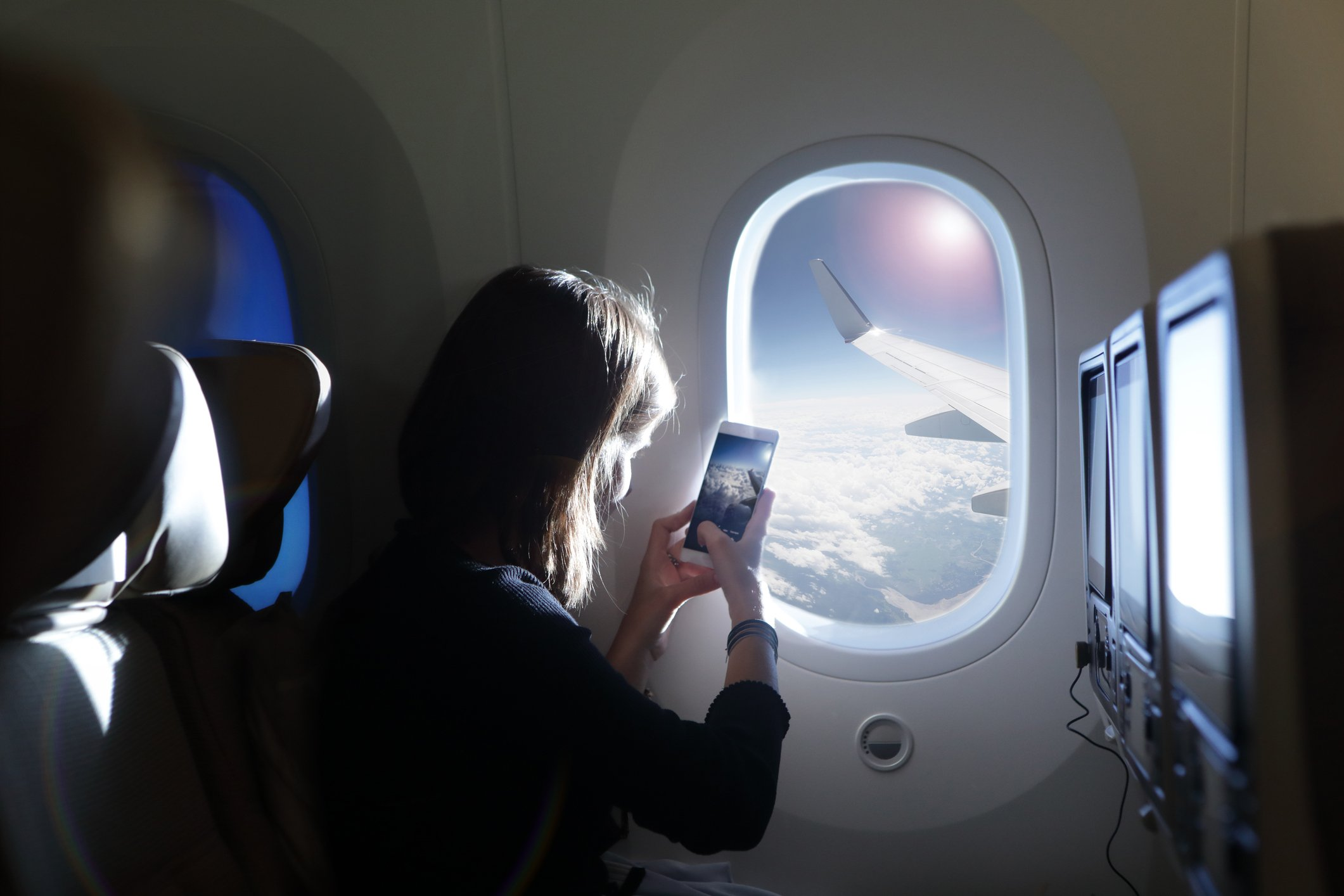 Girl taking photo out of airplane window | Photo: Getty Images