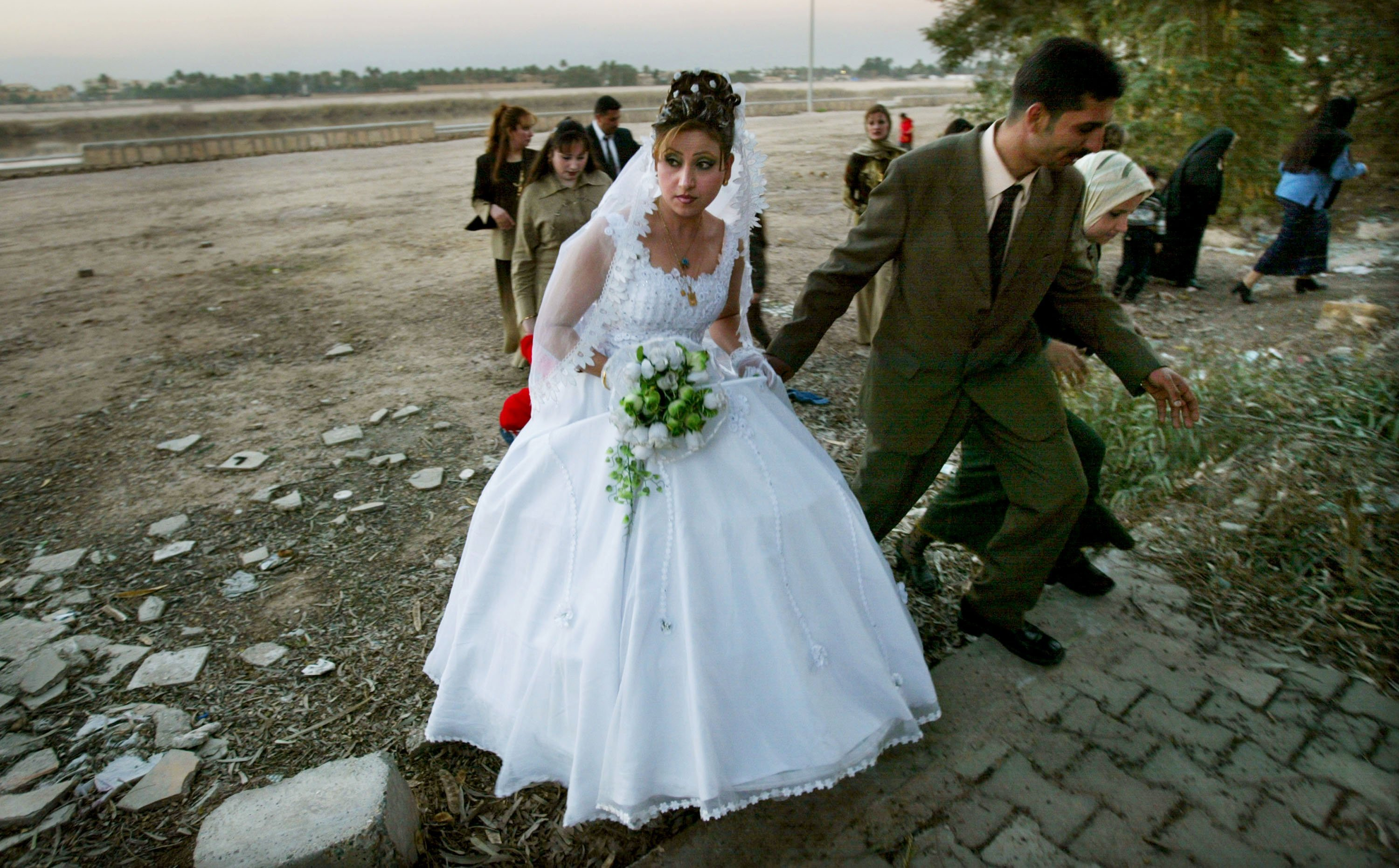 A newly married Iraqi couple walks away from the banks of the Tigris River after posing for photographs February 9, 2004 in Baghdad, Iraq. | Getty Images :photo