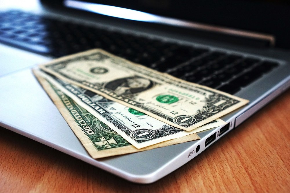 American Dollars displayed on top of a laptop. | Image: Pixabay.