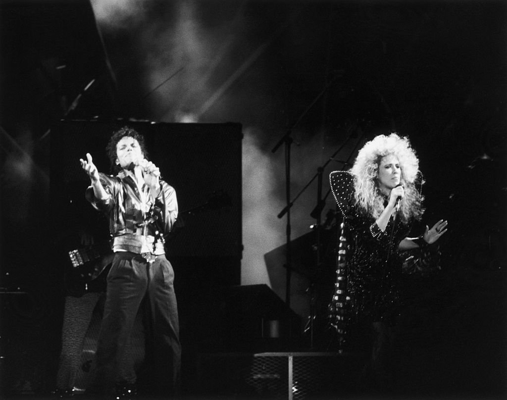 Michael Jackson teams up with backing singer Sheryl Crow for the duet 'I Just Can't Stop Loving You' during a 'Bad' World Tour concert in Japan | Photo: Getty Images