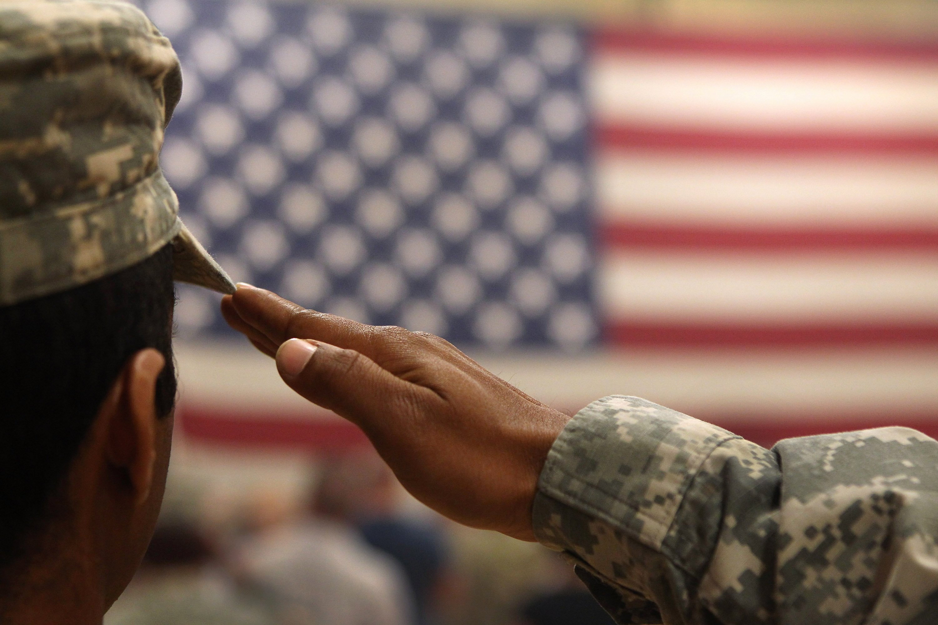 A soldier salutes the flag during a welcome home ceremony. | Photo: Getty Images