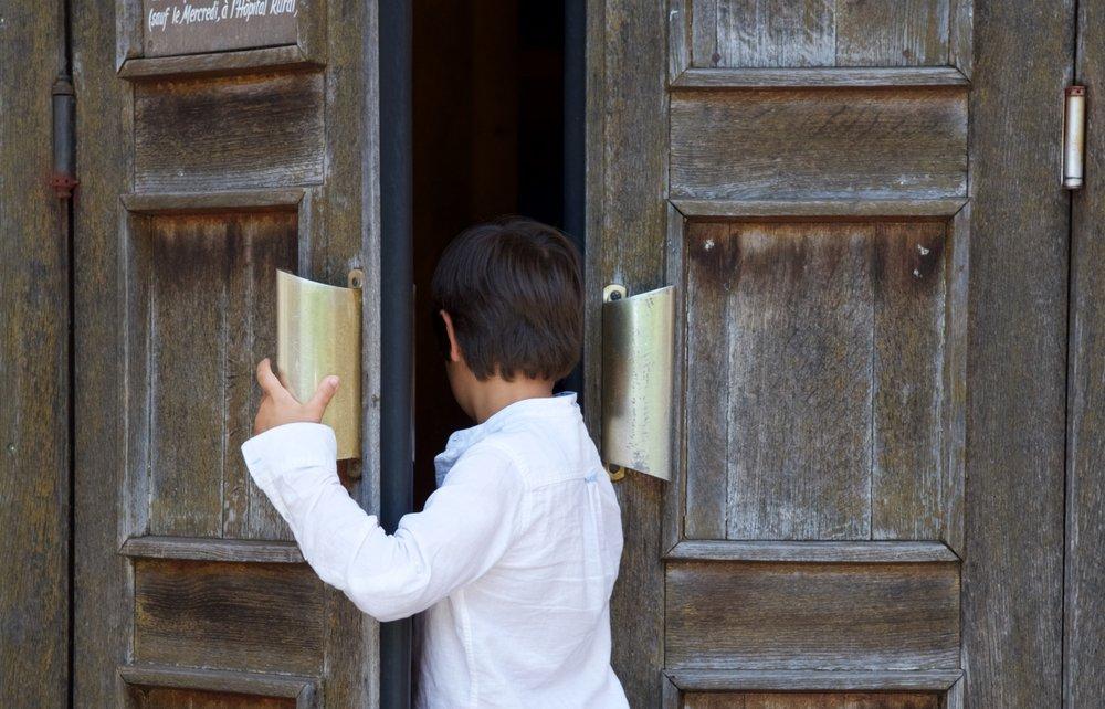 Un petit garçon entrant dans une église | Photo : Shutterstock