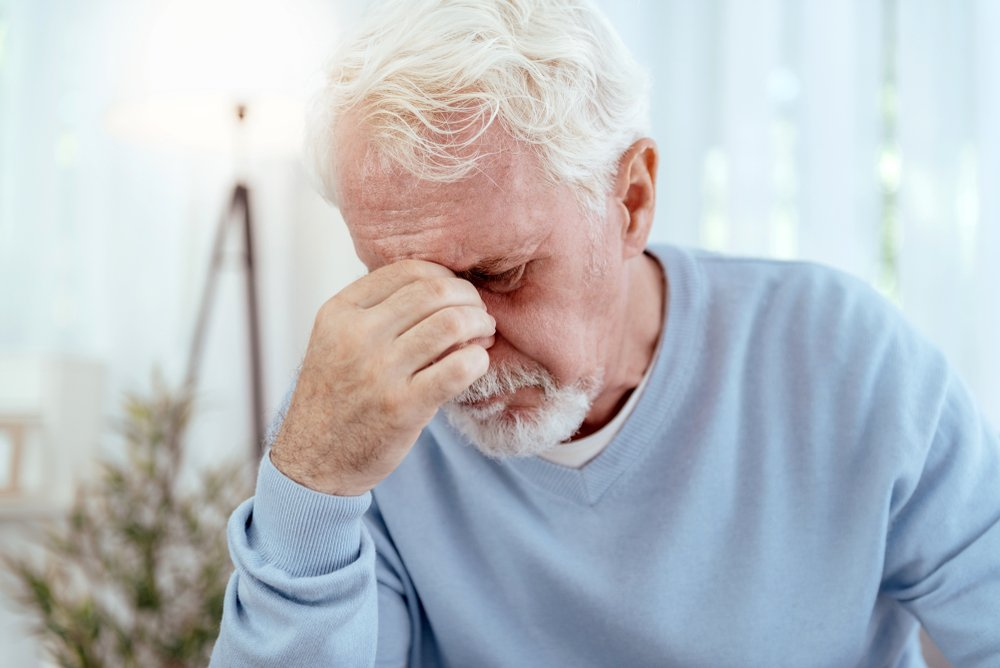 A disappointed senior man covering his face. | Photo: Shutterstock