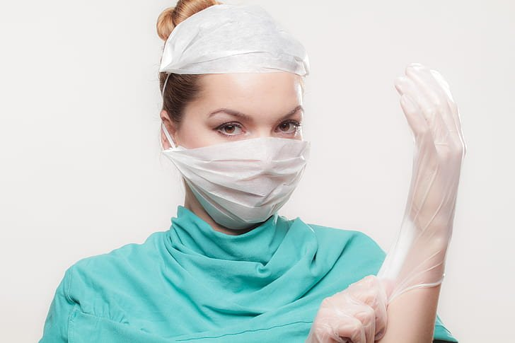 Doctor in scrubs wearing a latex glove and a face mask | Photo: PickPik