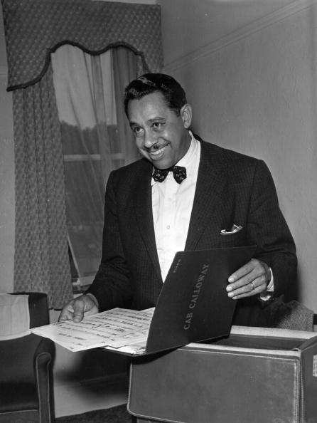 Cab Calloway opening a folio of music news | Photo: Getty Images