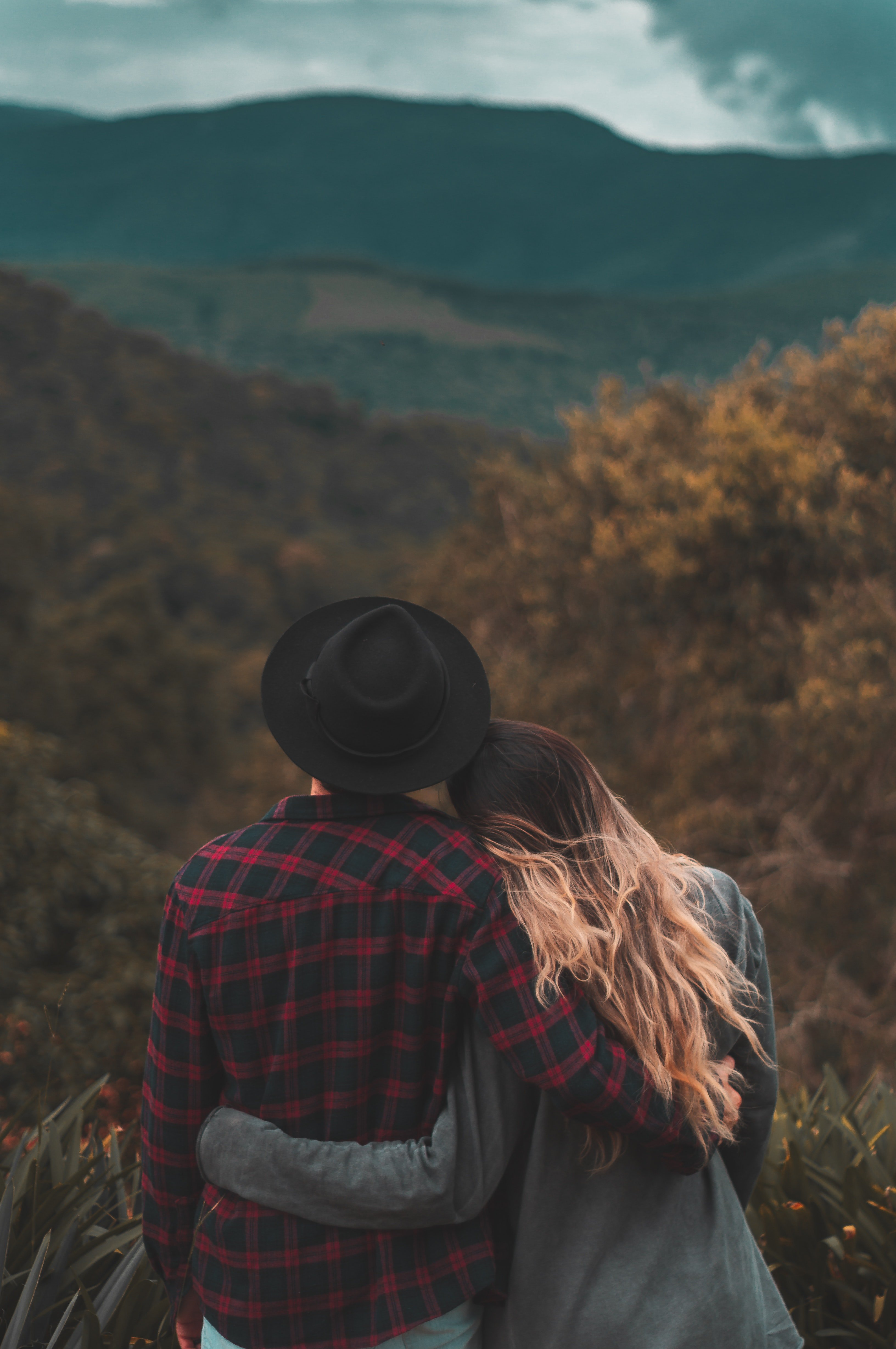 A couple standing on top of a hill with the woman resting her head on her man's shoulder   Source: Pexels